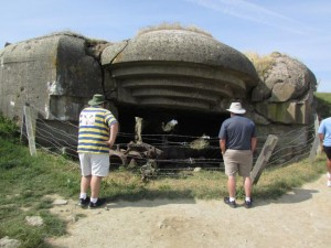 Father and two sons from Oklahoma look at one of the blasted bunkers above Arromanches-les-Bains
