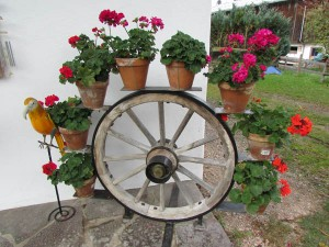 This homeowner has decorated using an old wagon wheel along with potted flowers near Kitzbuehl